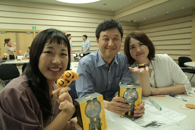 CJ CGV '리버스 멘토링' 현장에서 참가자들이 범블비 피규어를 들고 포즈를 잡고 있다