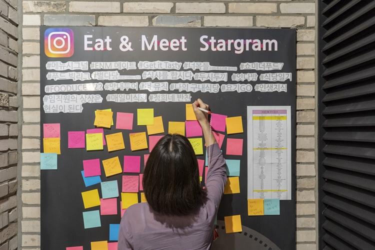 상암  ENM구내식당에 제안하는 게시판에 한 직원이 포스트잇으로 메뉴를 제안하고 있다