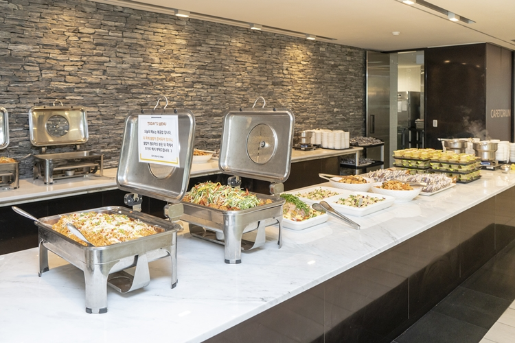 부페스타일의 그릇과 메뉴들이 테이블에 위에 나열되어 있다