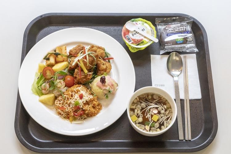 식판에 태국스타일의 볶음밥과 치킨이 올려져 있고 오뎅국물과 디저트 그리고 수저와 젓가락이 올려져 있다