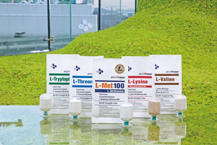 CJ제일제당의 친환경 발효공법으로 생산중인 5대 사료용 아미노산이 푸른 인조 잔디 위에 놓여져있다.