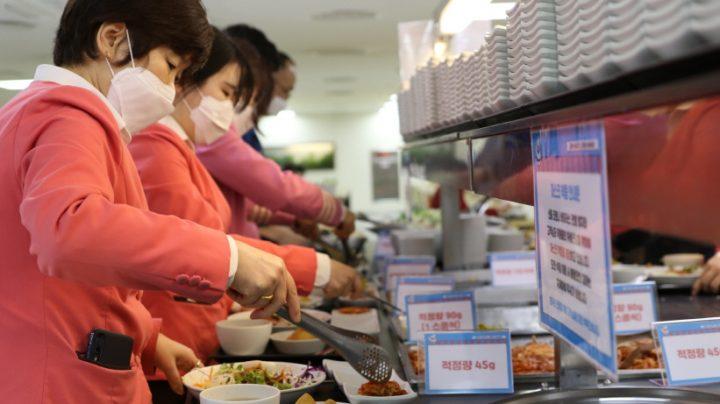 CJ프레시웨이가 위탁운영 중인 롯데월드 구내식당에서 직원들이 '제로웨이스트-제로헝거' 캠페인에 동참하기 위해 적정량 설명을 보면서 반찬을 담고 있다