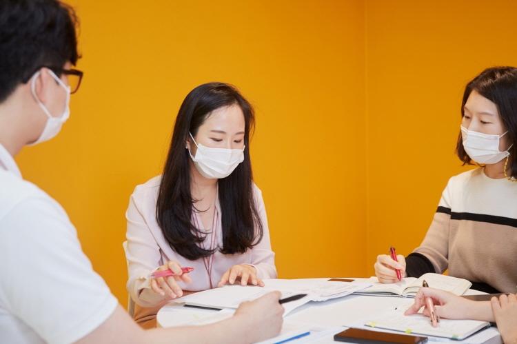 CJ제일제당 블러썸파크 내 노란색 벽으로 둘러싸인 회의실에서 김은혜 님과 팀원 두 명이 마스크를 쓴 채로 회의를 진행하고 있다.