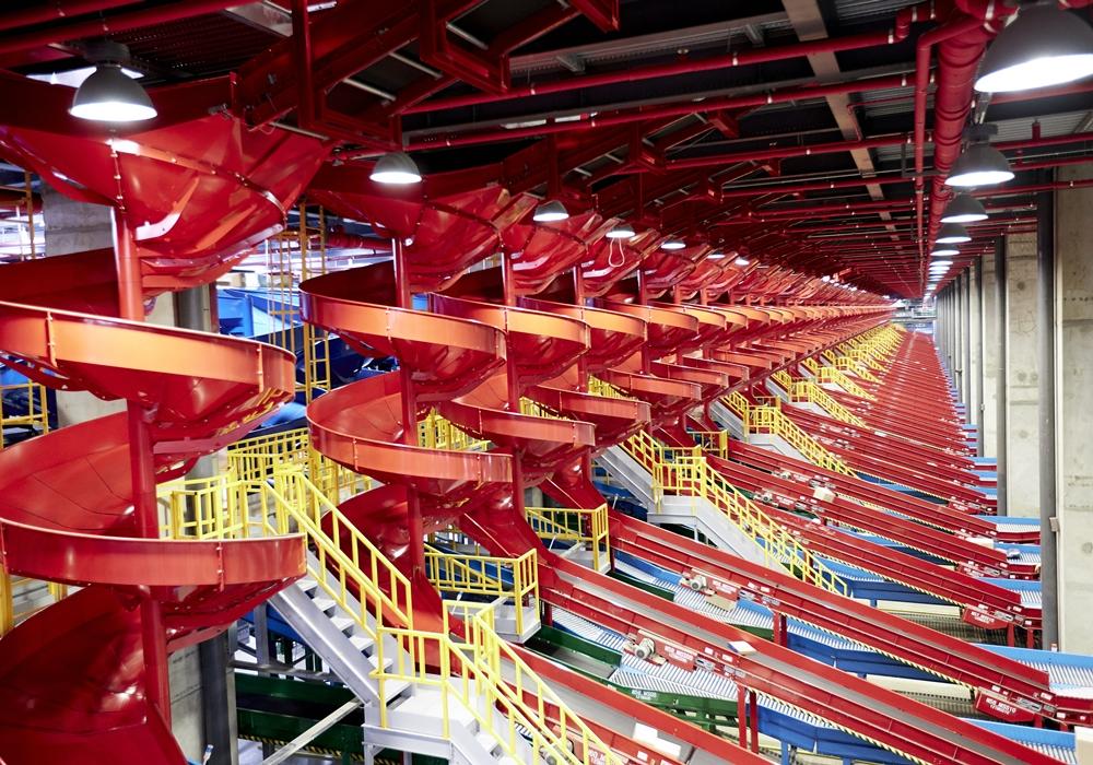 각각의 물류가 컨베이어 벨트를 통해 분류되고 각 지역 트럭에 담길 수 있게 설계된 CJ대한통운 허브 터미널 내부 모습이다. 붉은색으로 되어 있는 길을 따라 택배가 옮겨지는 모습을 볼 수 있다.