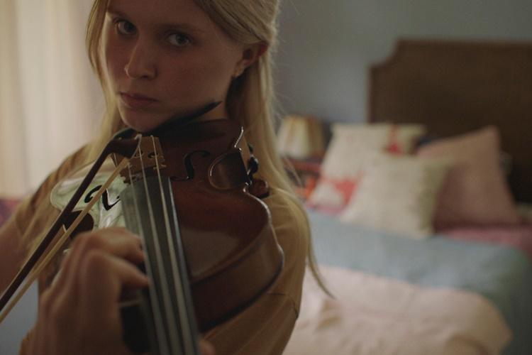 극중 밀라가 바이올린을 연주하는 모습이다. 특이하게도 그녀의 시선은 바이올린이 아닌 카메라를 향해 있다.