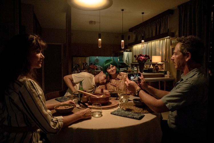 밀라의 부모가 식탁에 앉은 밀라와 모지스를 스마트폰 카메라로 촬영하는 모습이다.