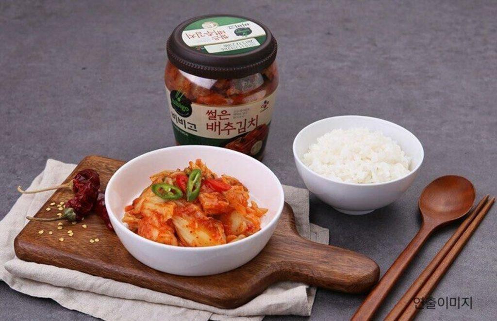 비비고 썰은 배추김치와 함께 차려진 흰쌀밥. 도마 위에는 비비고 썰은 배추김치는 그릇에 보기 좋게 담겨있고, 먹음직스럽게 보이기 위해 말린 고추도 놓여져 있다.