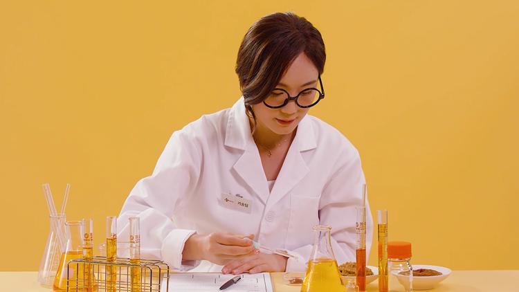 연구원 복을 입은 한 여성이 테이블 위에 놓인 연구실 물품 중 스포이드를 활용해 된장과 고추장의 최적 비율을 찾고 있다.