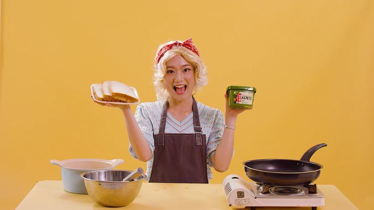 금색 가발을 쓴 한 여성이 왼손에는 쌈장을 오른손에는 접시에 담긴 식빵을 들고 있다. 그녀의 앞에는 가스버너와 프라이팬, 냅비 등이 놓여져 있다.