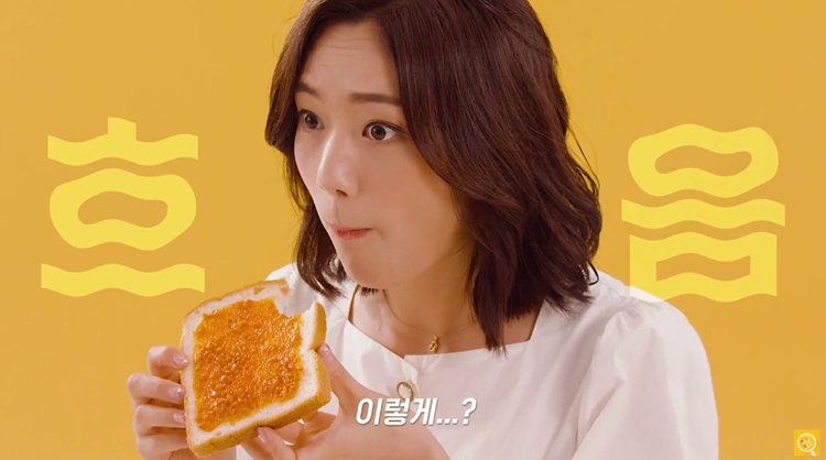 여자가 식빵에 쌈장을 발라 맛있게 먹는다.