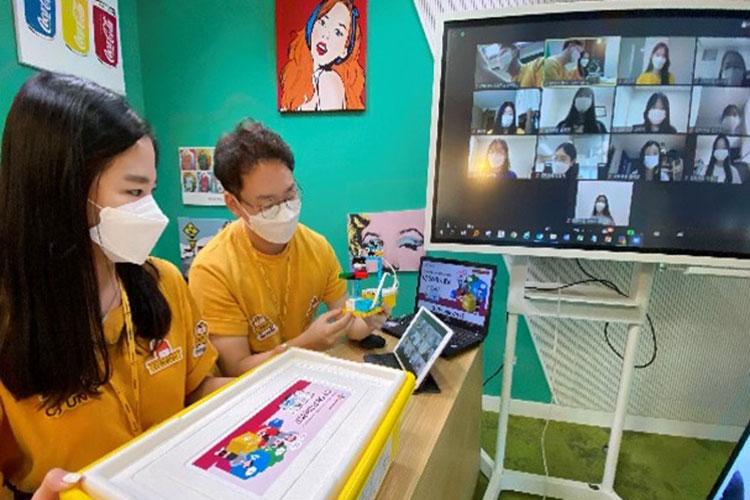 온라인으로 진행하고 있는 2020년 SW창의캠프 비대면 프로그램 'Girls can do IT' 현장 사진. 마스크를 쓴 채 노란색 옷을 입은 CJ올리브네트웍스 구성원들이 온라인으로 접속한 캠프 참여자들에게 교육을 하고 있는 모습이다.