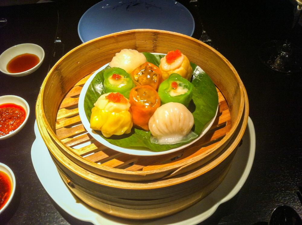전문 딤섬 식당에서 나올 법한 8종류의 딤섬 음식 이미지. 대나무 찜기 위 접시에 나뭇잎을 올리고 그 위에 딤섬을 올렸다.