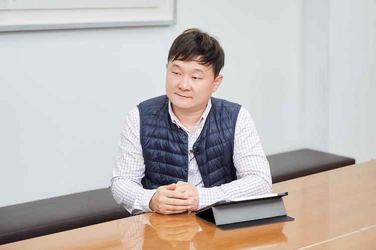MP 구축을 위해 새로운 소터 개발에 참여했다는 CJ대한통운 이규복님 사진. 그는 두 손 모아 인터뷰어의 질문에 경청하며 질문지를 띄어 놓은 아이패드를 보며 인터뷰를 이어나갔다.