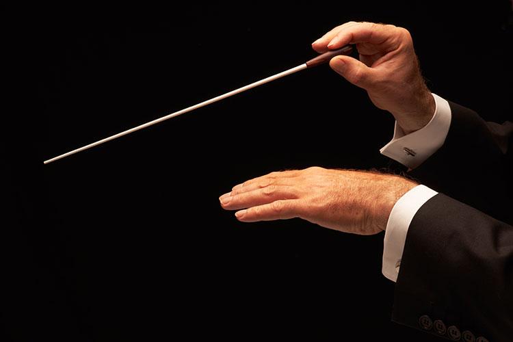 오케스트라 지휘자의 손 모습. 물류산업 내 정해진 시간에 정확한 위치로 물건을 이동시키고 관리하는 것 시스템은 흡사, 마치 수많은 악기와 연주자로 구성된 오케스트라의 지휘자를 연상케 한다는 내용에 맞게 오케스트라 지휘자의 손 이미지를 삽입했다.