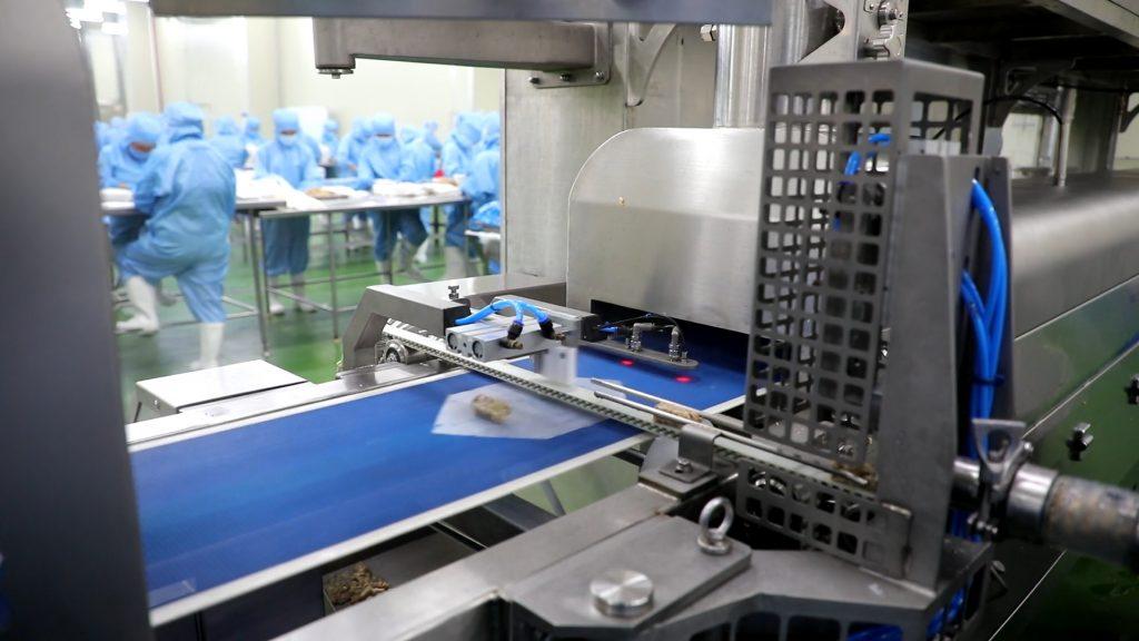 CJ제일제당이 세계 최초로 개발한 라이스 스프링롤 성형기 사진. 성형기 내 컨베이어 벨트 위에 라이스 페이퍼가 놓여져 있고, 그 위에 내용물이 담겨져 있다. 기계 뒤에는 공장 직원들이 스프링롤을 만들기 위해 분주히 움직이고 있다.