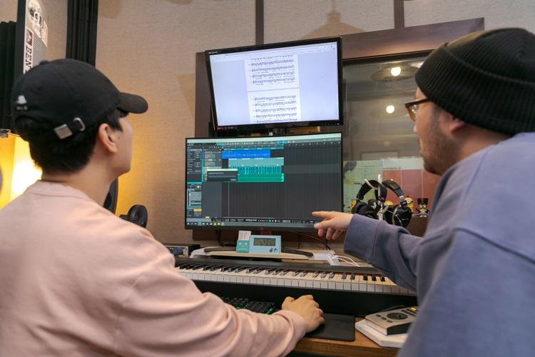 이번 행사 합창곡인 'We will meet again'을 공동작업하는 두 작곡가의 모습. 나이브 작곡가의 의견에 따라 제인스 작곡가가 음악을 수정하고 있다.