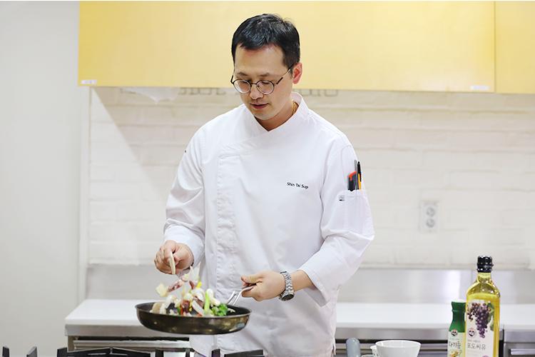 신태섭 셰프가 사내 주방에서 메뉴 개발을 위해 왼손에는 프라이펜을 오른존은 뒤집개를 잡고 볶음 음식을 만들고 있다.
