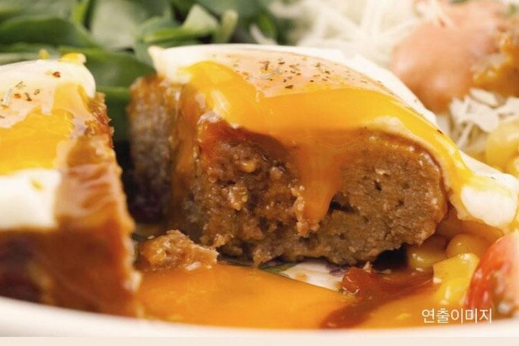 고메 함박스테이크 조리 후 반을 잘라 놓은 이미지. 촉촉함과 육즙이 살아있는 스테이크 단면과 위에 올려져 있는 계란 노른자가 흘러내려 최고의 배합 맛을 보여준다.함박스테이크의 맛은 촉촉함. 이를 위한 포장 기술은 필수!