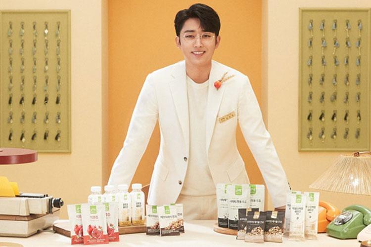 CJ ENM 식품PB '오하루 자연가득'이 제품이 놓여져 있는 테이블 뒤에 배우 손호준이 흰색 옷을 입고, 안경을 쓰고, 미소를 짓고 있다.