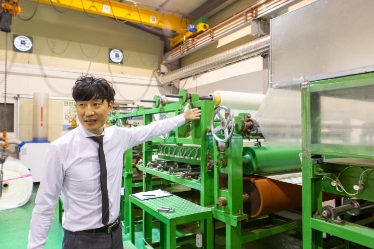 생산설비 왼편에 선 조주영 대표가 오른 쪽을 쳐다보며 왼손으로 기계를 가리키고 있다.