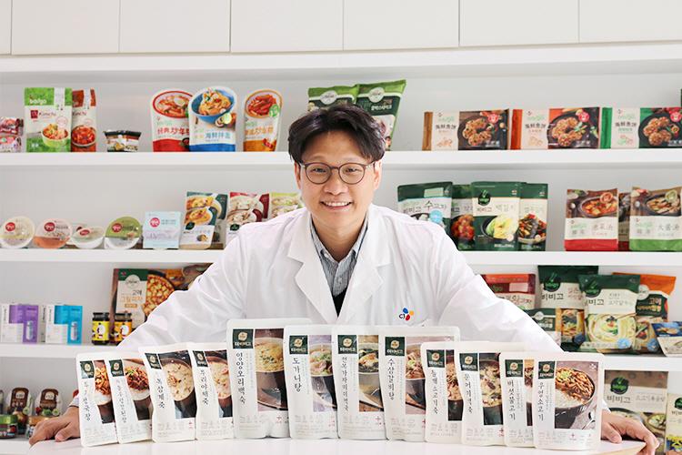건강한 HMR을 원하는 소비자들을 위해 '더비비고'를 탄생시킨 CJ제일제당 식품연구소 HMR팀 정우영 연구원의 모습. 정우영 연구원은 흰색 연구원 옷을 입고 더비비고 12종 제품 뒤에서 서 서 미소를 지으며 카메라를 쳐다보고 있다.