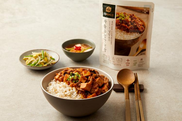 '더비비고' 차돌우렁강된장 파우치 포장 제품과 제품 내용물이 그릇에 담겨 있고, 반찬으로 나온 콩나물과 물김치가 그릇에 담겨 있는 사진이다.