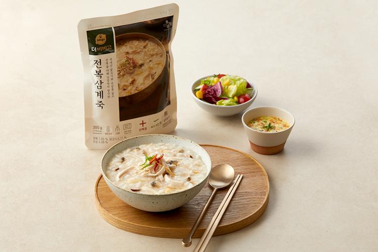 '더비비고' 전복삼계죽 파우치 포장 제품과 제품 내용물이 그릇에 담겨 있고, 반찬으로 나온 샐러드와 계란찜도 그릇에 담겨 있는 사진이다.