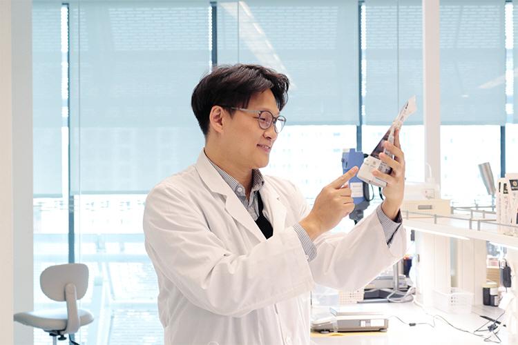 CJ제일제당 연구실에서 더비비고 파우치 제품을 들고 이를 바라보는 정우영 영구원의 모습이다.