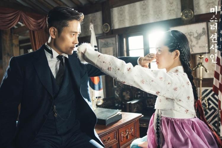 tvN 드라마 '미스터 션샤인' 중 두 주인공인 이병헌과 김태리가 서로의 정체를 의심하게 되는 장면으로, 왼쪽에 검은 정장을 입은 이병헌, 오른쪽 한복을 입은 김태리가 손을 서로의 입에 가져가 눈을 확인하고 있는 모습이다.
