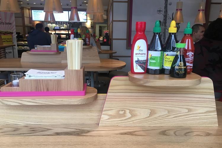 'Itsu'레스토랑에 테이블탑 소스로 비치된 초고추장의 모습. 나무로 된 선반에 놓여있는 초고추장 옆으로 다양한 향신료들이 놓여있다.