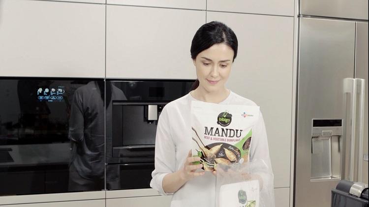 한 여성이 주방에서 AI추천 'Recipick'으로 주문한 비비고 만두 제품을 받고 미소를 머금은 모습이다.