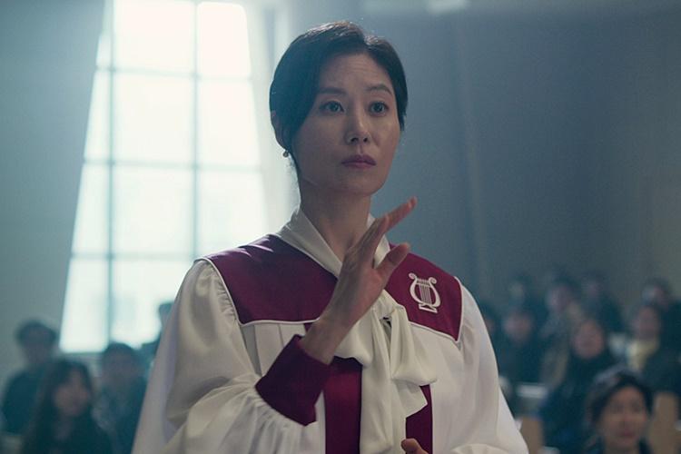 영화 '세 자매'에서 둘째인 미연 역을 맡은 문소리가 한 교회의 성가대 일원으로서 성가대 옷을 입고 박자에 맞춰 지휘를 하고 있는 모습이다.