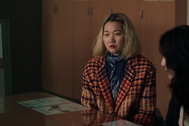 영화 '세 자매'에서 막내 미옥 역을 맡은 장윤주가 술기운이 느껴지는 붉은 얼굴로 테이블에 앉아 멍을 때리고 있는 모습이다.