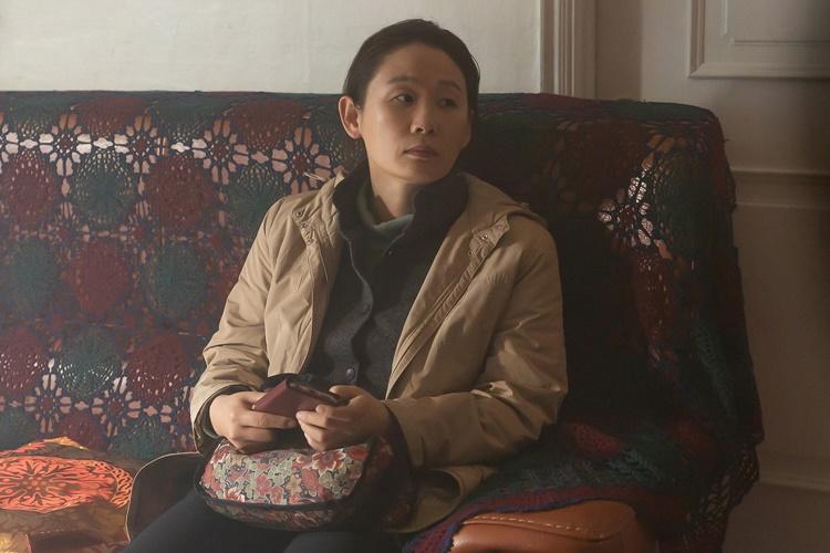 영화 '세 자매'에서 첫째 희숙 역을 맡은 김선영이 집 안 소파에 앉아 핸드폰을 만지작 거리며 미안한 표정으로 한 곳을 응시하고 있다.
