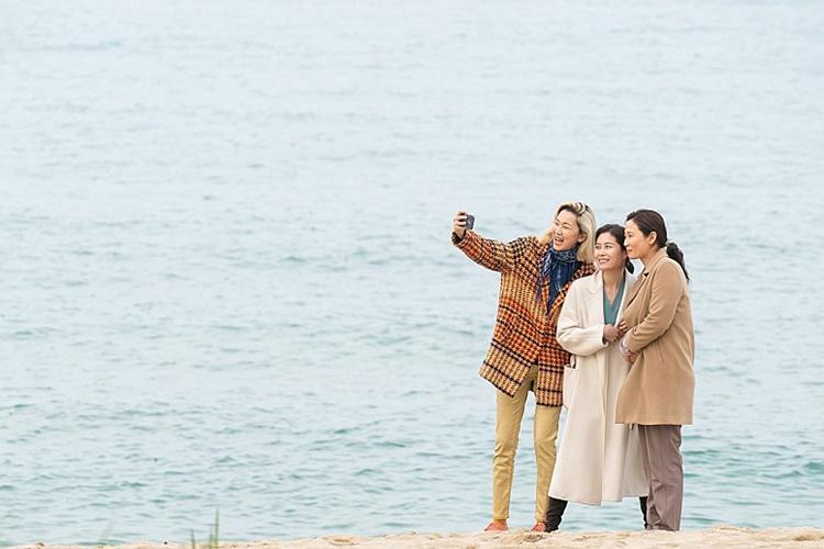 극중 한 장면으로, 장윤주, 문소리, 김선영이 해변에 서서 스마트폰으로 사진을 촬영하고 있는 모습이다.