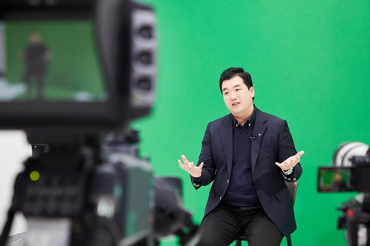 CJ대한통운 블루택배 담당자 커뮤니케이션팀 CSV 윤한득 님이 녹색을 배경으로 의자에 앉아 영상 카메라 앞에서 인터뷰를 하는 모습을 보여주고 있다.