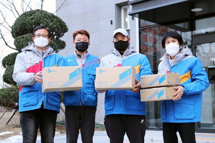 CJ대한통운 블루택배 배송원들의 모습으로, 총 4명(남성 3명, 여성 1명) 모두 CJ대한통운 유니폼을 입고 택배 상자를 든채 카메라를 항해 포즈를 취하고 있다.