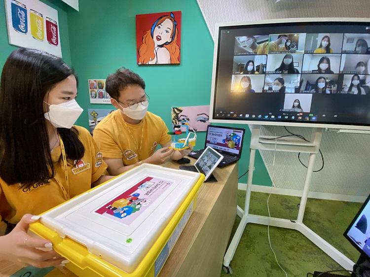 CJ SW창의캠프 봉사단 CJ UNIT이 학생들과 비대면 디지털 SW코딩 수업을 진행하고 있는 모습으로, TV, 노트북, 태블릿 화면을 통해 노란색 유니폼을 입은 봉사단 CJ UNIT이 의자에 앉아 관련 제작물을 통해 코딩 수업을 하고 있다.