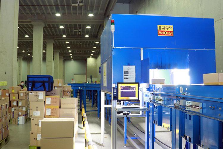 의약품 전담물류센터에 설치된 첨단스캐너의 모습으로, 365일 24시간 적정온도를 유지하고 있는 물류센터에서 전국으로 수송될 의약품들이 자동 분류된다. 현장 사진에는 레일을 통해 스캐너를 지나가는 물품이 보인다.