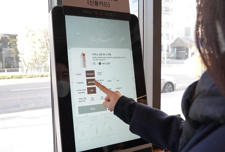 폴바셋 삼성강남타운점에서 고객이 키오스크로 음료를 주문하고 있는 모습으로, 아이스크림 딸기 라떼 선택 후 사이즈, 우유변경, 아이스크림 토핑 변경 등 각 선택란을 검지손가락으로 체크하고 있다.