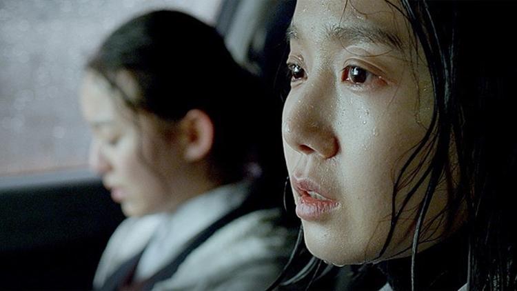 차 안에 비에 젖은 두 명의 여자가 앉아있는 모습. 왼쪽에 머리를 묶고 시선을 아래로 떨구고 있다. 오른 쪽에는 눈물고인 희주의 얼굴이 보인다.