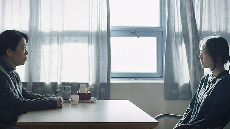 책상을 사이에 두고 영남과 희주가 앉아있는 모습. 그 뒤에 있는 창문으로 밝은 빛이 쏟아져 들어오고 있다.