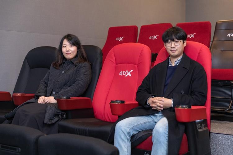 왼쪽부터 차례로 이지혜PD와 정브르가 4DX영화관 좌석 한 칸을 띄우고 앉아 카메라를 응시하는 모습