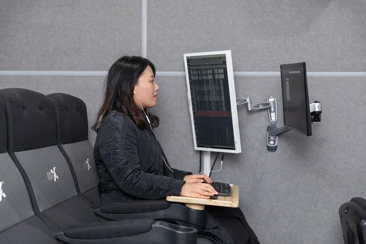 4DX좌석에 앉아 직접 효과를 테스트 해보기도 하면서 작업을 하고 있는 이지혜 PD의 모습. 이지혜PD는 이어폰을 끼고 왼쪽 세로 모니터와 오른쪽 모니터를 번갈아 보며 작업하고 있다.