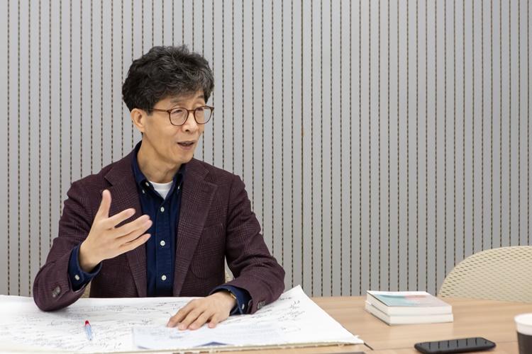 '디아스크' 홍성돈 대표가 테이블에 앉아 인터뷰에 응하는 모습으로, 테이블 위에는 제품 관련 메모를 적은 종이와 펜, 그리고 책 두 권 등이 놓여져 있다.