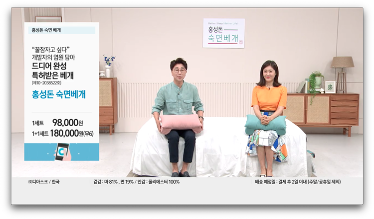'홍성돈 숙면베개'가 CJ오쇼핑부문 홈쇼핑 방송에서 소개되고 있는 모습으로, 남성, 여성 쇼호스트 모두 침대에 앉아 각각 핑크색, 그린색 제품을 들고 방송을 진행하고 있다.