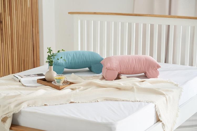 침대 위에 그린, 핑크 '홍성돈 숙면베개'가 놓여져 있다.