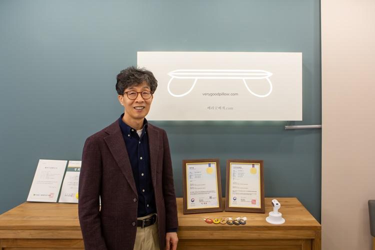 '디아스크' 홍성돈 대표가 '홍성돈 숙면베게'를 만들어 받은 특허증 및 상장을 놓은 테이블과 회사 로고가 박혀있는 조형물을 배경으로 포즈를 취하고 있다.