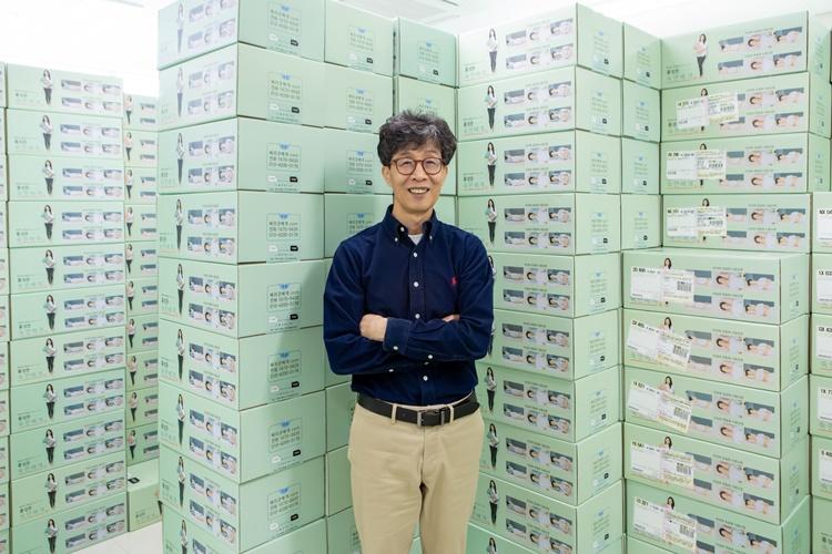 '디아스크' 홍성돈 대표가 '홍성돈 숙면베게'를 포장 제품이 쌓여있는 곳에서 팔짱을 낀 채 포즈를 취하고 있다.
