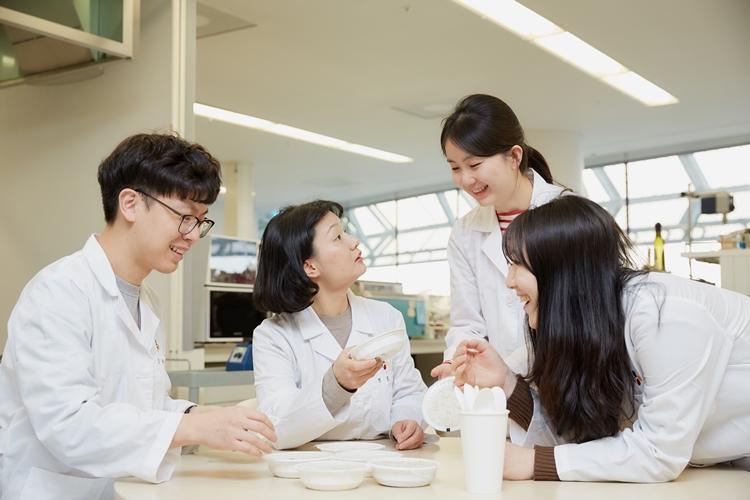 CJ제일제당 블러썸파크 연구실에서 정효영 연구원과 세 명의 팀원이 테이블에서 햇반에 대한 이야기를 나누고 있다. 모두 연구복을 입었고, 정효영 연구원은 햇반을 들고 있다.